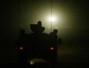 A HUMVEE IS SILHOUETTED AS IT LEADS A CONVOY AT NIGHT IN NORTHERNKUWAIT.