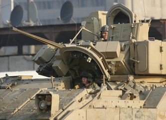 U.S. soldiers ride in a Bradley fighting vehicle on their way out of their camp to conduct a patrol in Baghdad