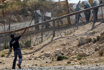 A Palestinian protester hurls rocks during a violent demonstration in the West Bank village of Bilin