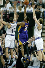 LAKERS BRYANT SHOOTS BETWEEN KINGS CHRISTIE AND TURKOGLU.