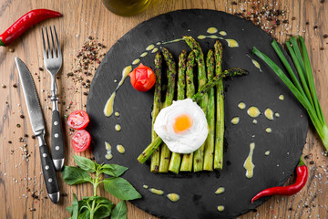 Asparagus cooked on a grill with fried egg sauce and tomato.