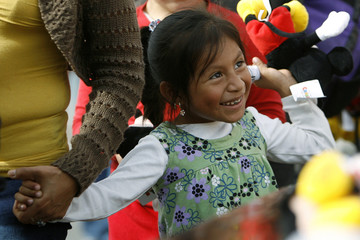 Four-year-old Caryna Cavina Alcavaz smiles after receiving a stuffed Mickey Mouse toy at Fred Jordan Mission's 66th annual Family Christmas Celebration and Toy Party in Los Angeles