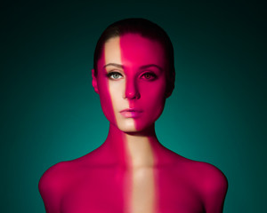 Fashion art portrait of elegant naked young woman with color light on her face