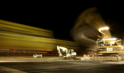 Workers use heavy equipment to remove a 15-metre long slice of Frankfurt airport's 60-metre wide run..