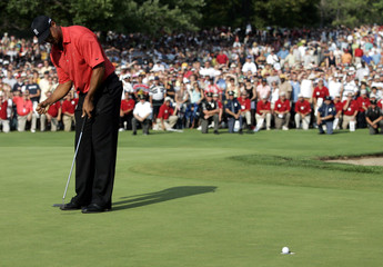 Tiger Woods makes his putt during the final round of the Buick Open golf tournament in Grand Blanc