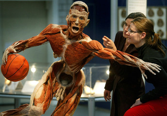 Two women look at plastinated human specimen depicting a basketball player at Gunther von Hagen's ex..