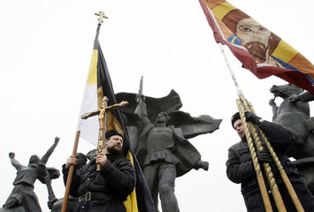 Protesters with Orthodox symbols stand next to a monument to revolutionary workers during a demonstration in central Moscow