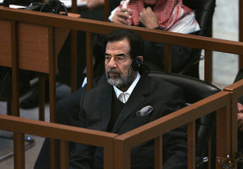 Saddam Hussein listens to a translation through headphones in court during the continuation of his 'Anfal' genocide trial in Baghdad