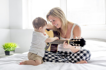 Smiling woman with guitar sitting on the bed with child