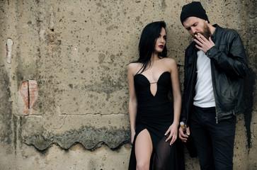 Pretty fashion woman in sexy black dress and man smoking