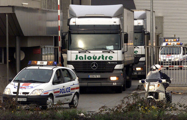 French police escort trucks carrying euro coins as they leave the national mint in Pessac near Borde..