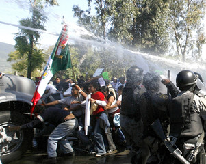 Members of the Popular Assembly of Oaxaca (APPO) attempt to stop a police truck armed with water cannons in Oaxaca