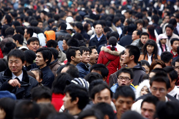 A man yawns in crowd of tens of thousands of passengers at Guangzhou Railway Station