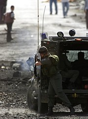 ISRAELI SOLDIER SHOOTS RUBBER BULLET AT PALESTINIAN DEMONSTRATORS.