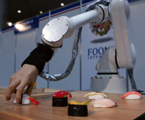 Robot with soft pneumatic fingers handles plastic sushi during demonstration at exhibition in Tokyo