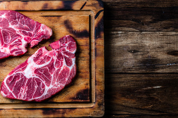 Two raw beef marbled meat steak on wooden cutting board, rustic background. Top view