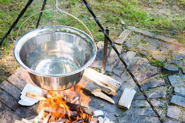 Cooking food on fire outdoors. Cooking outdoors in cast-iron cauldron.