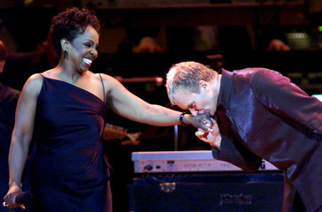 STING KISSES GLADYS KNIGHTS HAND AT RAINFOREST BENEFIT.