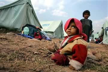 A Kashmiri boy sits on the ground at an evacuation tent camp in Muzaffarabad, capital of Pakistan-ad..