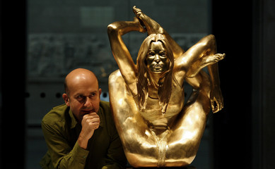 Artist Marc Quinn poses for photographers as he unveils his gold sculpture of model Kate Moss entitled 'Siren' at the British Museum in London