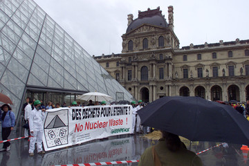 A TOURIST STOPS TO LOOK AT GREENPEACE DEMONSTRATION IN FRONT OF LOUVREMUSEUM IN PARIS.
