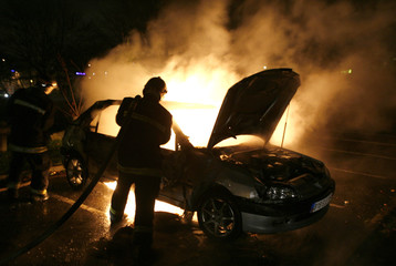 French firefighters extinguish a burning car in the Paris suburb of Villiers le Bel