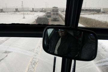 Driver of press bus touring with U.S. Democratic presidential candidate Senator Barack Obama sits behind motorcade after it was stopped by a crossing freight train in Boone