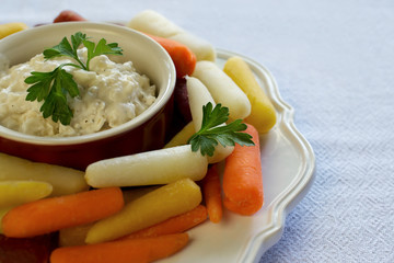 Closeup on plate of baby rainbow carrots and onion dip on white tablecloth, viewed at dinner angle, with copyspace - healthy eating concept