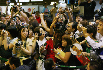 JAPANESE FANS SCRAMBLE TO TAKE PICTURES AS BECKHAM AND REAL MADRIDARRIVE AT TOKYO'S NARITA AIRPORT.
