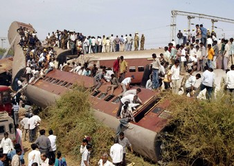 Onlookers climb onto the wreckage of a train in Samlaya village in Ahmedabad.