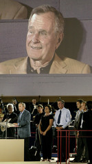 US PRESIDENT GEORGE W.BUSH SPEAKS WITH HIS SIBLINGS IN FRONT OF AN IMAGE OF THEIR FATHER IN HOUSTON.