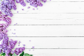 Floral pattern made of blue lilac branches and petals on white wooden background. Flat lay, top...