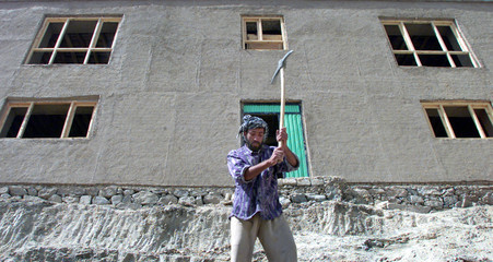 AFGHAN MAN WORKS NEAR NEW HOUSE ON THE OUTSKIRTS OF KABUL.