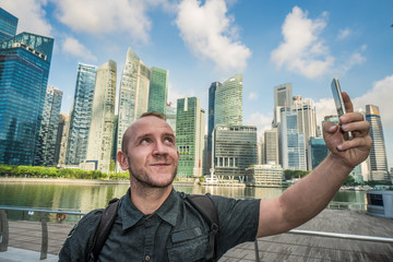 Handsome man holding smartphone for self-portrait photo with view of modern skyscrapers during summer travel vacation