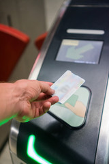 Closeup of man's hand scanning ticket at the metro station entrance machine