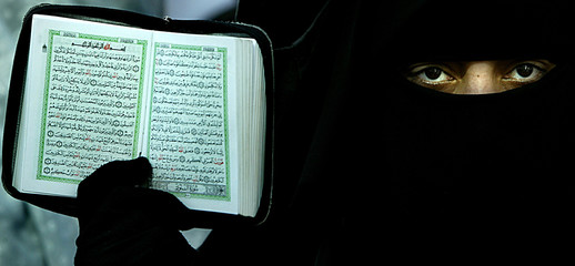 """A Hamas woman supporter holds a copy of the """"Koran"""" as she protests in Gaza City."""