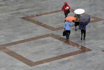 People walk under umbrellas across Munich's main square Marienplatz during a rainy weather