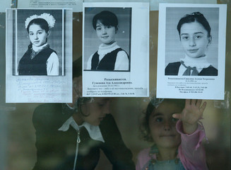 Two girls talks to each other behind the glass with the pictures of still missing hostages in the ...