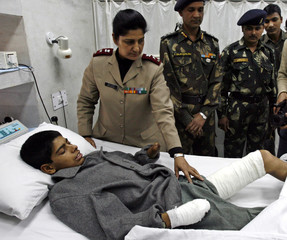 Indian army paramedic shows bandaged wounds of Kashmiri victim of landmine explosion in Srinagar