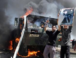 Iraqi Shi'ite supporters of cleric Moqtada al-Sadr celebrate near a burning U.S. Army truck in the S..