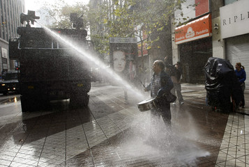 A teacher is hit by police water cannon as he plays a drum during a rally in Santiago