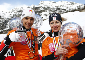 Grabner and Guenther of Austria celebrate their overall Snowboard World Cup trophy after the parallel giant slalom race at the Snowboard World Cup Finals in Chiesa Valmalenco