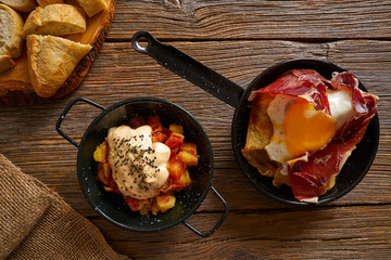 Tapas from spain broken eggs and bravas