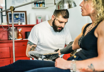 Professional bearded tattooer preparing blond woman for special tattoo session inside ink trendy studio