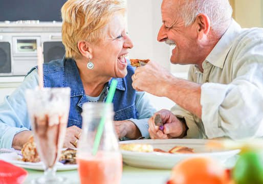 Happy senior couple having fun eating breakfast during summer travel vacation