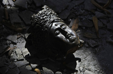 The head of a statue of Buddha lies among the ruins of destroyed Erwang Temple in earthquake-hit Dujiangyan