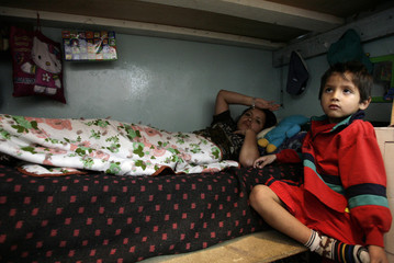Paquita Mena of Ecuador rests on her bed next to her son in her cell at Women's Prison of Quito
