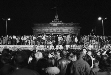 East and West German citizens celebrate as they climb the Berlin wall at the Brandenburg gate in Berlin