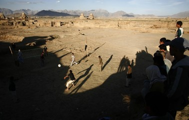 Afghan men play volleyball on the outskirts of Kabul