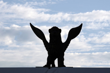 A golden lion statue is silhouetted in front of the Cinema Palace in Venice